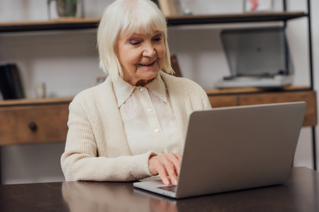 happy senior woman sitting at table and typing on laptop at home Фото со стока