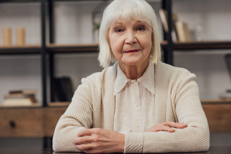 senior woman with grey hair and folded hands sitting looking at camera at home Imagens