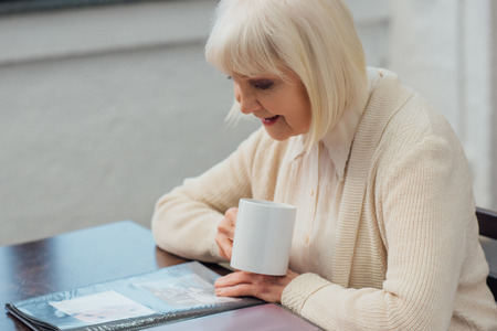 senior woman sitting at table and looking at photo album while drinking coffee at home Stock Photo