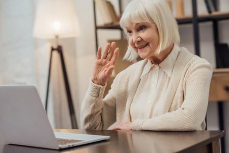 Sonriente mujer mayor sentada en el escritorio de la computadora y saludando mientras tiene una videollamada en casa