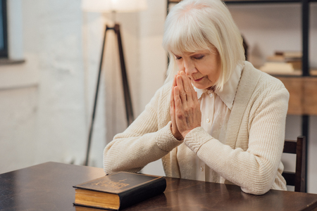 concentrated senior woman sitting and praying in front of holy bible at home Reklamní fotografie