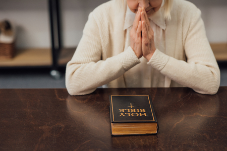 cropped view of senior woman sitting and praying in front of holy bible at home