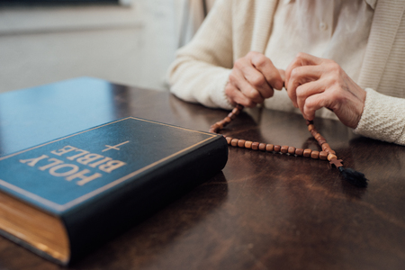 partial view of senior woman sitting at table with rosary and holy bible at home