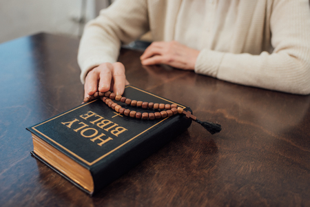 cropped view of senior woman sitting at table with rosary and holy bible at home Stok Fotoğraf - 116321001