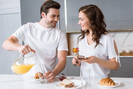 handsome man holding jug with orange juice and looking at girlfriend in kitchen 版權商用圖片