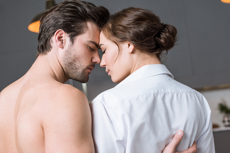 adult couple embracing at home with closed eyes