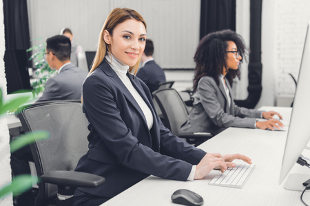 beautiful young businesswoman using desktop computer and smiling at camera in office Stock Photo