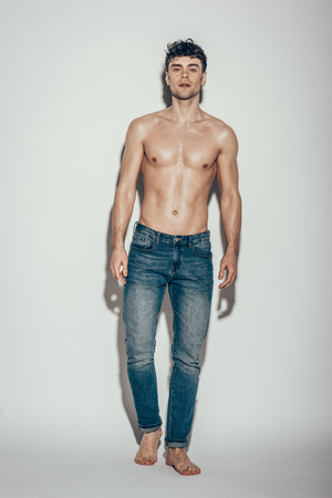 shirtless macho in jeans posing on grey