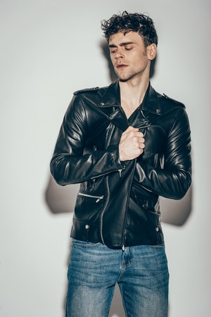 handsome man posing in black leather jacket on grey