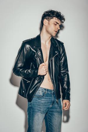 guapo, elegante, hombre, posar, en, jeans, y, chaqueta de cuero negro, en, gris Foto de archivo