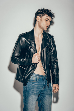 gut aussehender stilvoller Mann posiert in Jeans und schwarzer Lederjacke auf Grau Standard-Bild