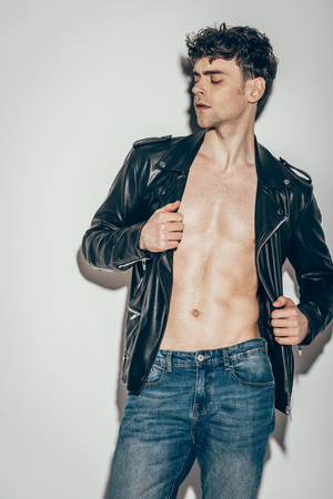 young sexy man posing in jeans and black leather jacket on grey
