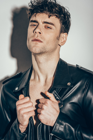 portrait of sexy man posing in black leather jacket on grey