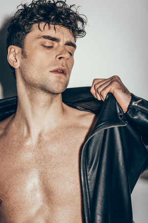 handsome young man wearing black leather jacket on grey