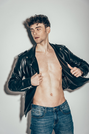 handsome stylish man posing in black leather jacket on grey