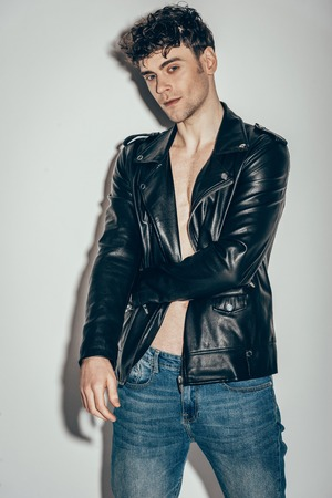 stylish man posing in jeans and black leather jacket on grey