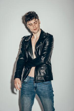 stylish rocker posing in black leather jacket on grey