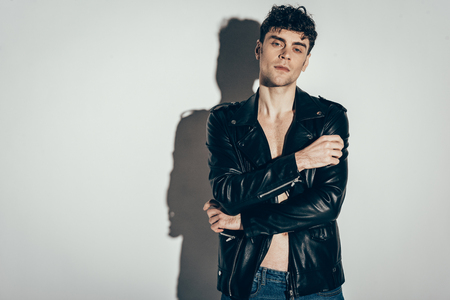 handsome sexy man posing in trendy leather jacket on grey
