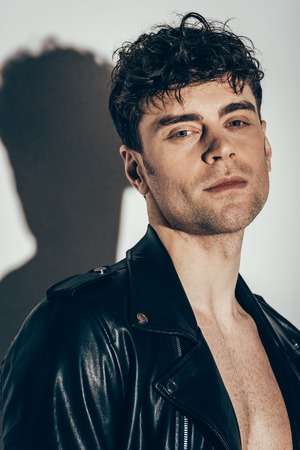 portrait of stylish sexy man posing in black leather jacket on grey