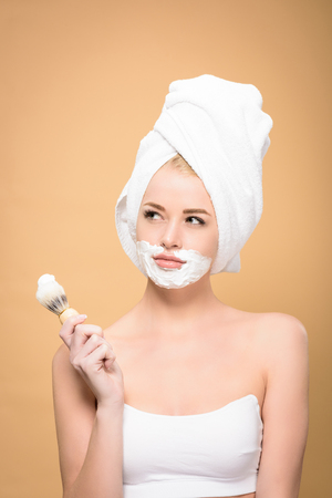 woman with towel on head and shaving cream on face holding shaving brush and looking away isolated on beige
