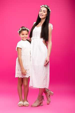6ae7226254 full length view of beautiful happy mother and daughter in white dresses  and floral wreaths hugging