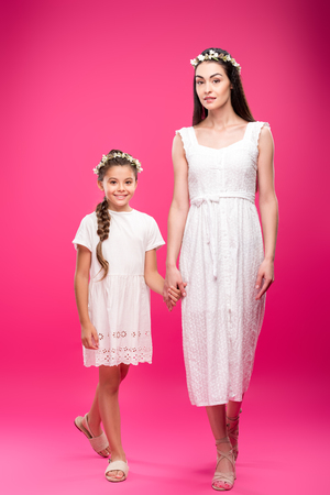 e8da052fff beautiful happy mother and daughter in white dresses and floral wreaths  holding hands and smiling at