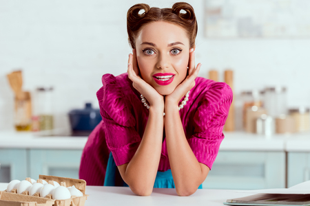 Pretty pin up girl leaning up on kitchen table and looking at camera Stock Photo
