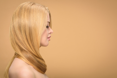 Side view of gorgeous blonde woman looking down on beige background