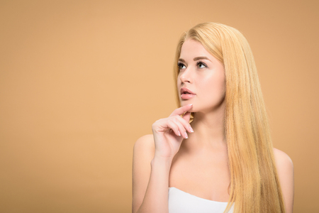 Pensive blonde girl looking up and touching chin Stock Photo