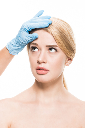 cropped shot of cosmetologist in latex glove touching forehead of naked young woman isolated on white Stok Fotoğraf