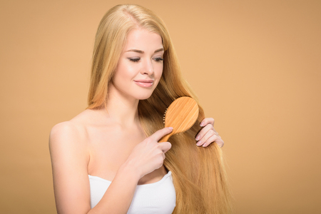 Joyful blonde girl brushing straight hair with smile