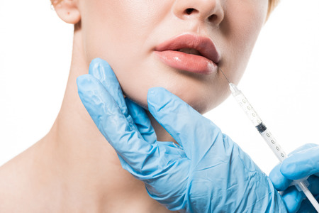 cropped shot of young woman receiving beauty injection in lips isolated on white