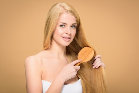Happy blonde woman brushing long hair on golden background