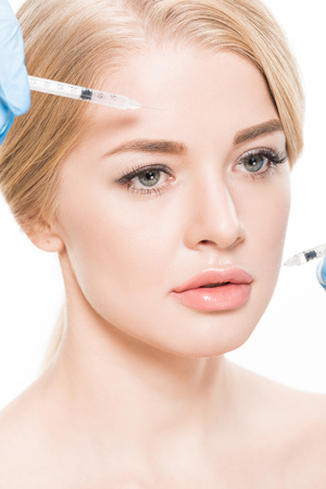 cropped shot of cosmetologist making beauty injections to attractive young woman isolated on white