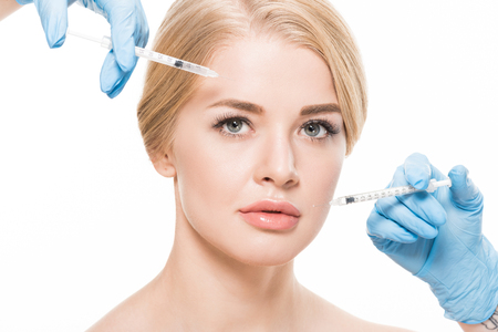 cropped shot of young woman receiving beauty injections in face isolated on white