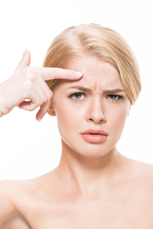 unhappy naked woman pointing at wrinkles on forehead and looking at camera isolated on white Imagens