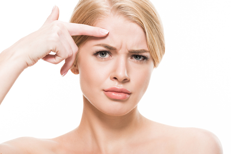 unhappy young woman pointing at wrinkles on forehead and looking at camera isolated on white