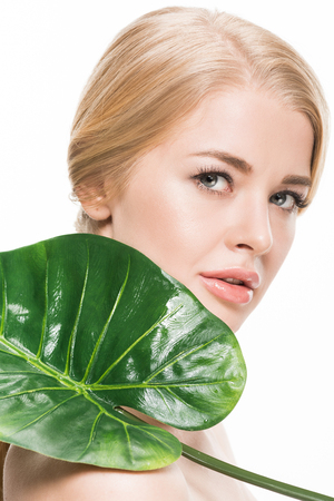 beautiful young woman holding green tropical leaf and looking at camera isolated on white
