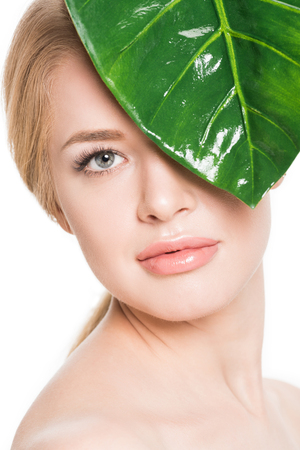 attractive naked girl with green leaf near eye looking at camera isolated on white Stock Photo