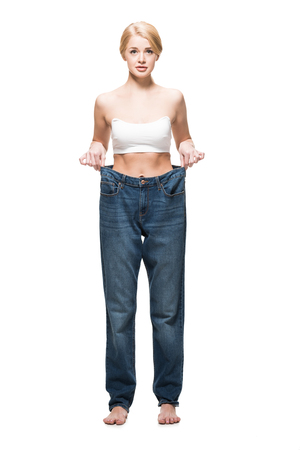 full length view of barefoot slim girl wearing oversized jeans and looking at camera isolated on white