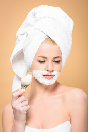 woman with towel on head and shaving cream on face holding shaving brush and looking down isolated on beige