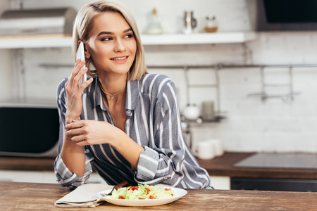 selective focus of attractive woman eating and using smartphone