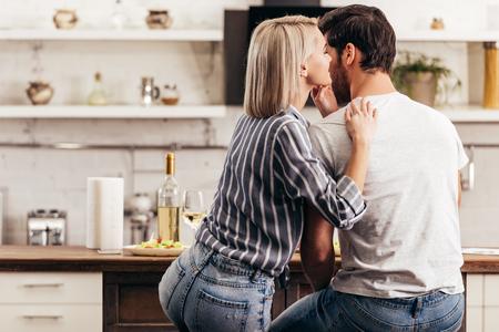 boyfriend and attractive girlfriend hugging in kitchen