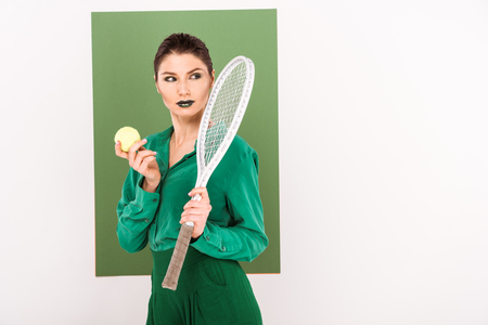beautiful fashionable woman holding tennis ball and racket while posing with sea green on background Stok Fotoğraf
