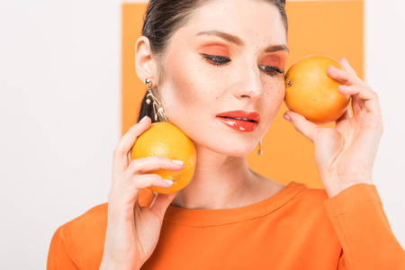 beautiful stylish woman holding oranges and posing with turmeric on background Banco de Imagens