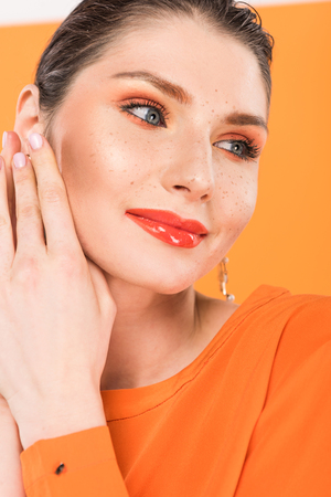 portrait of smiling fashionable woman posing with turmeric on background