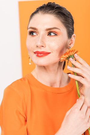 beautiful stylish young woman holding flower and posing with tumeric on background Stock Photo