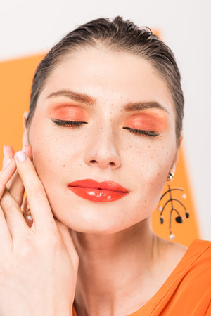 beautiful fashionable young woman posing with eyes closed and tumeric on background