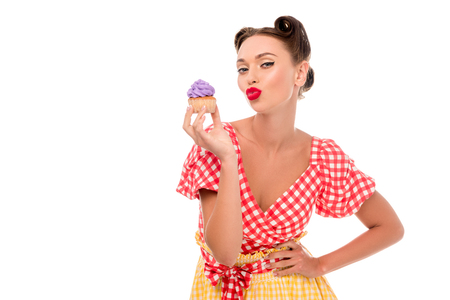 Stylish pin up girl demonstrating cupcake with purple cream and holding hand on hip isolated on white