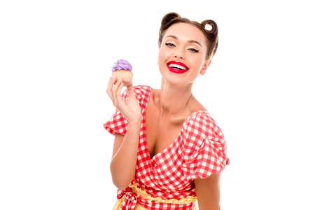 Stylish pin up girl demonstrating cupcake with purple cream isolated on white